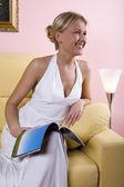 Lächelnde frau mit der mode-magazin auf ihrem knie — Stockfoto