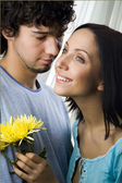 Young loving brunette man embracing his smiling girlfriend holding yellow flowers — Stock Photo