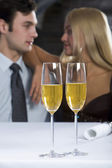 Two champagne glasses on the table and loving couple on the background — Stock Photo