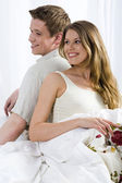 Young laughing couple lying in the bed — Stock Photo