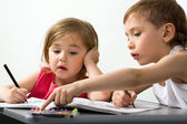 Careful brother shows to his smaller sister the color of felt-tip pen which is better for drawing — Stock Photo