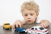 Curly blond boy playing with cars on the gray table — Stock Photo