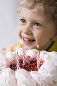 Happy blond boy with birthday cake looking at the candles — Stock Photo