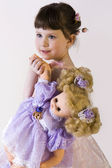 Sweet brunette little girl in pink dress holding her doll — Stock Photo