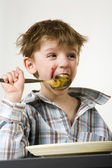 Little boy with a spoon in mouth — Stock Photo