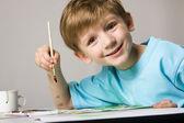 Bonito rapaz sorridente é sentar à mesa e com o pincel na mão — Fotografia Stock