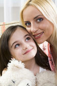 Smiling beautiful blond mother caring for her daughter holding her beloved bear — Stock Photo