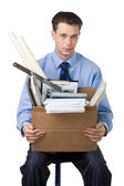Portrait of businessman holding box with documents sitting on the chair — Stock Photo