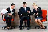 Image of business sitting on the red armchairs and working on the background of brick wall — Stock Photo
