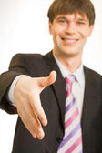 Businessman giving a hand for handshake — Stock Photo