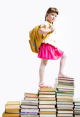 Image of serious schoolgirl standing on book stairs and looking at camera — Stock Photo