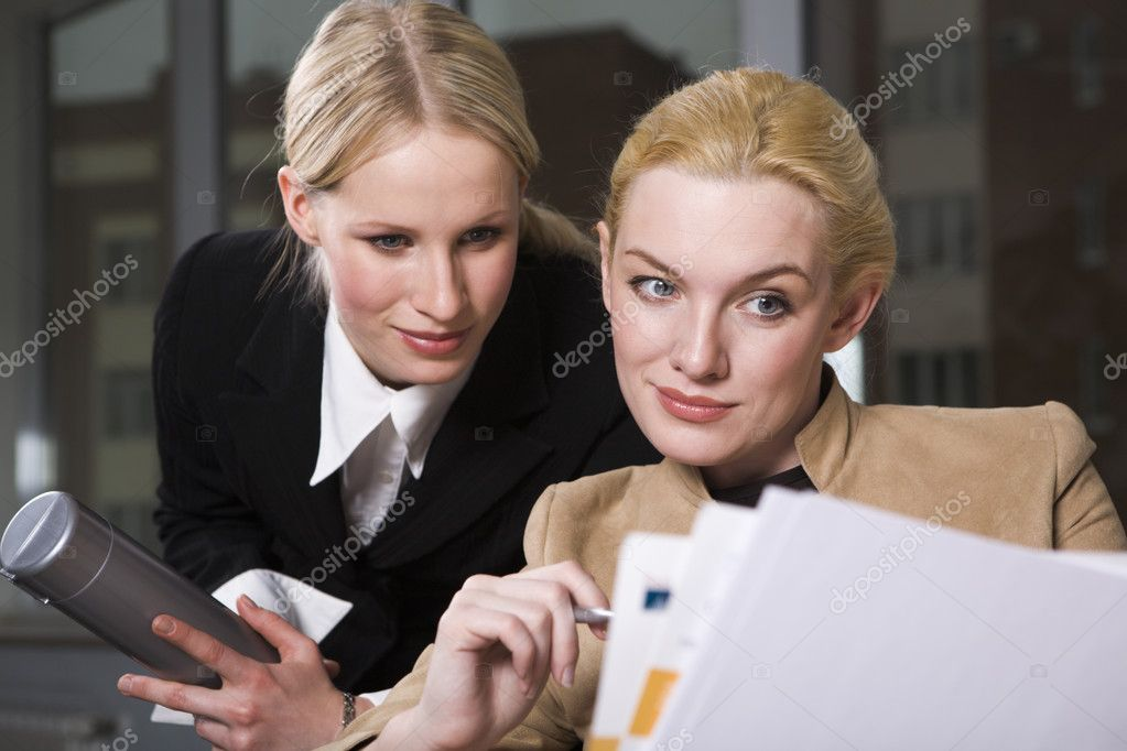 Two pretty women are reading an official record — Stock Photo #10710577
