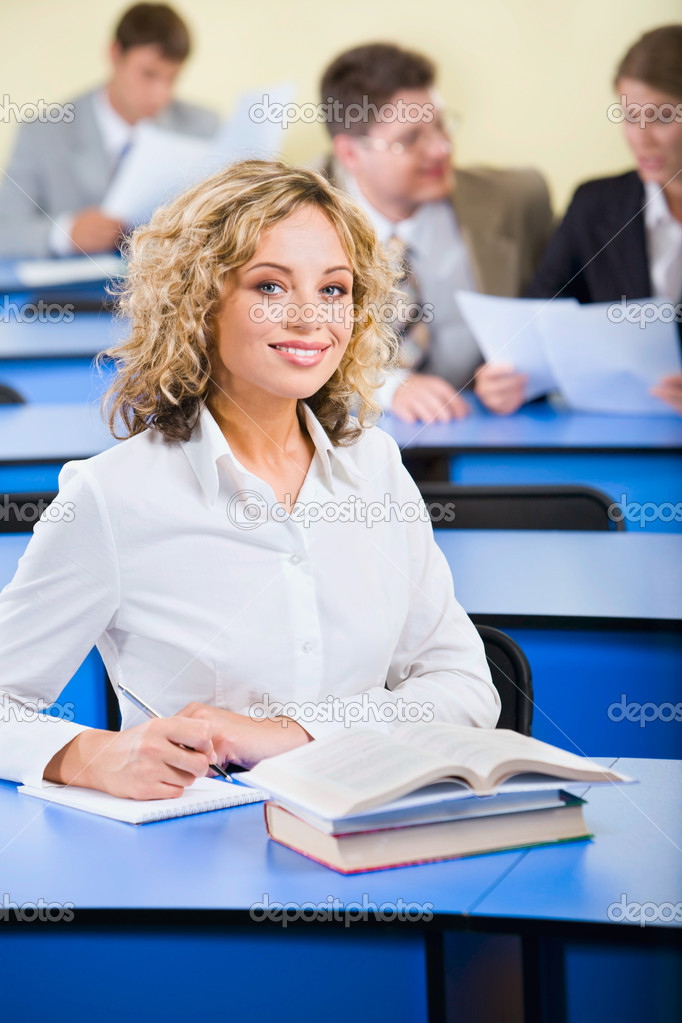 Portrait of beautiful smiling student sitting at a blue table and writing a composition — Stock Photo #10711853