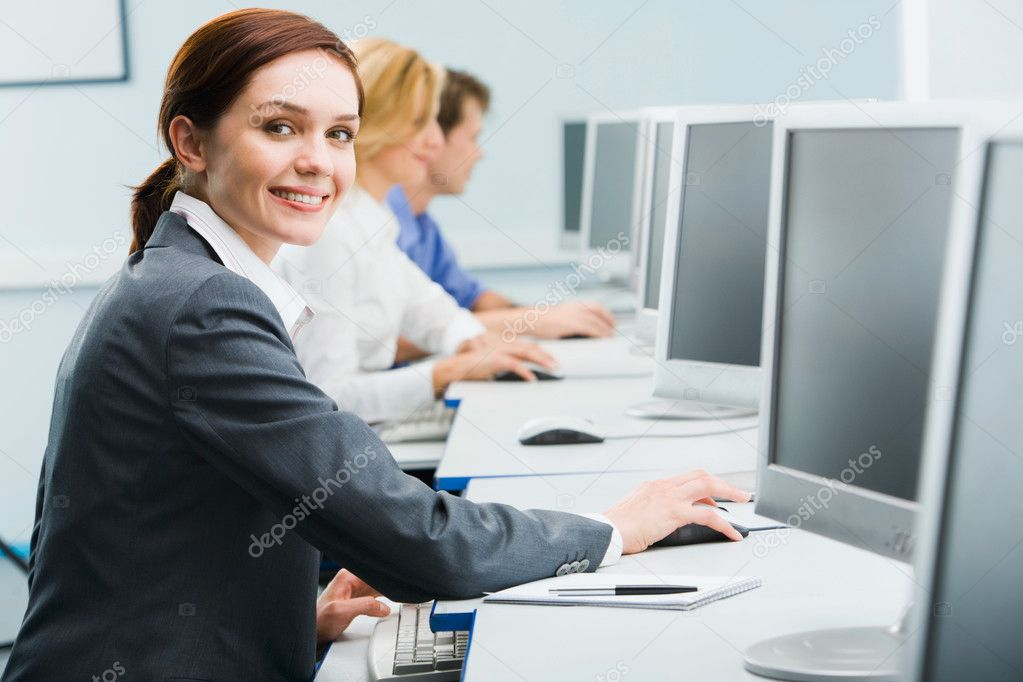 Portrait of busy woman sitting at the computer table and touching computer mouse on the background of businesspeople  Stock Photo #10711859