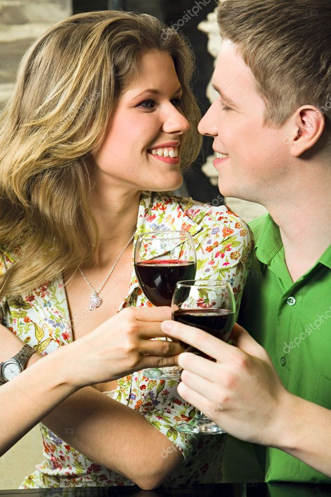 Young couple is holding the glasses of red wine in a restaurant — Stock Photo #10713078