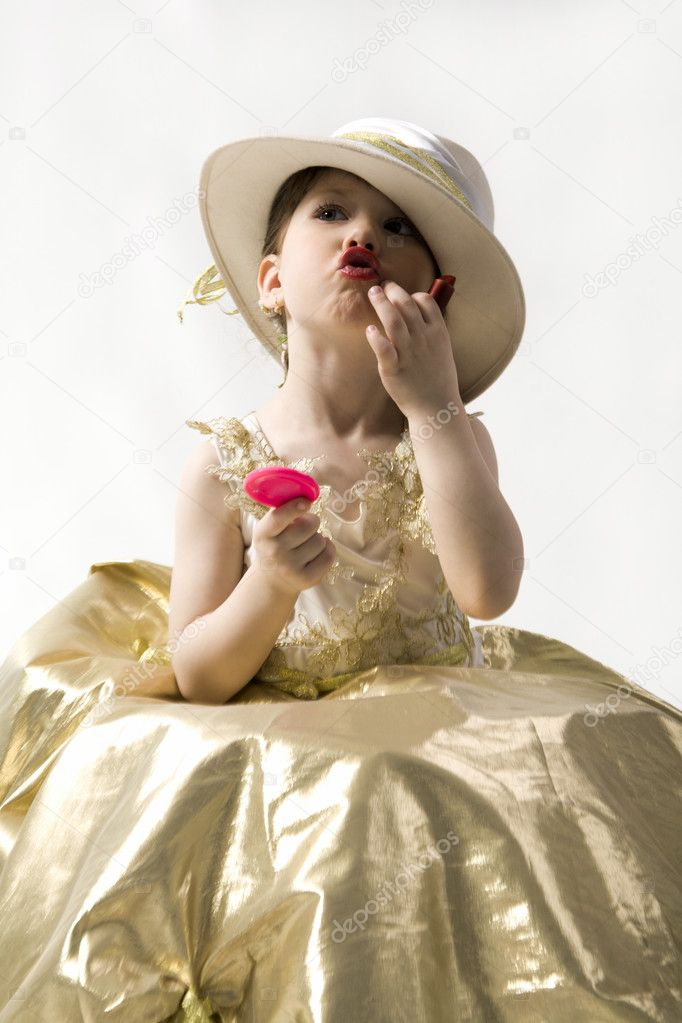 Sweet brunette little girl in light goldish dress and white hat making up her lips — Stock Photo #10713123