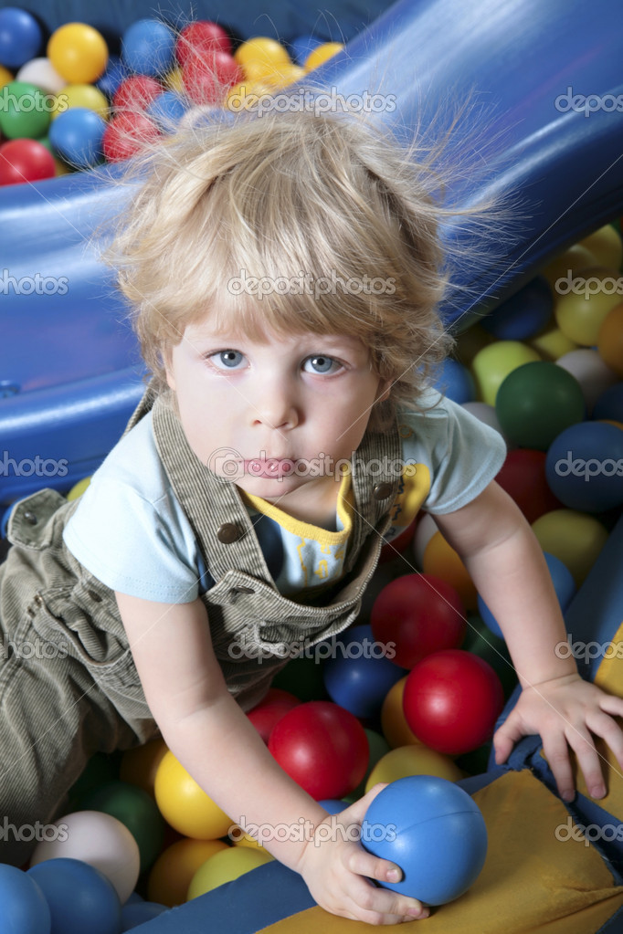 Lad seated on colorful balls and looking at camera  — Stock Photo #10713141