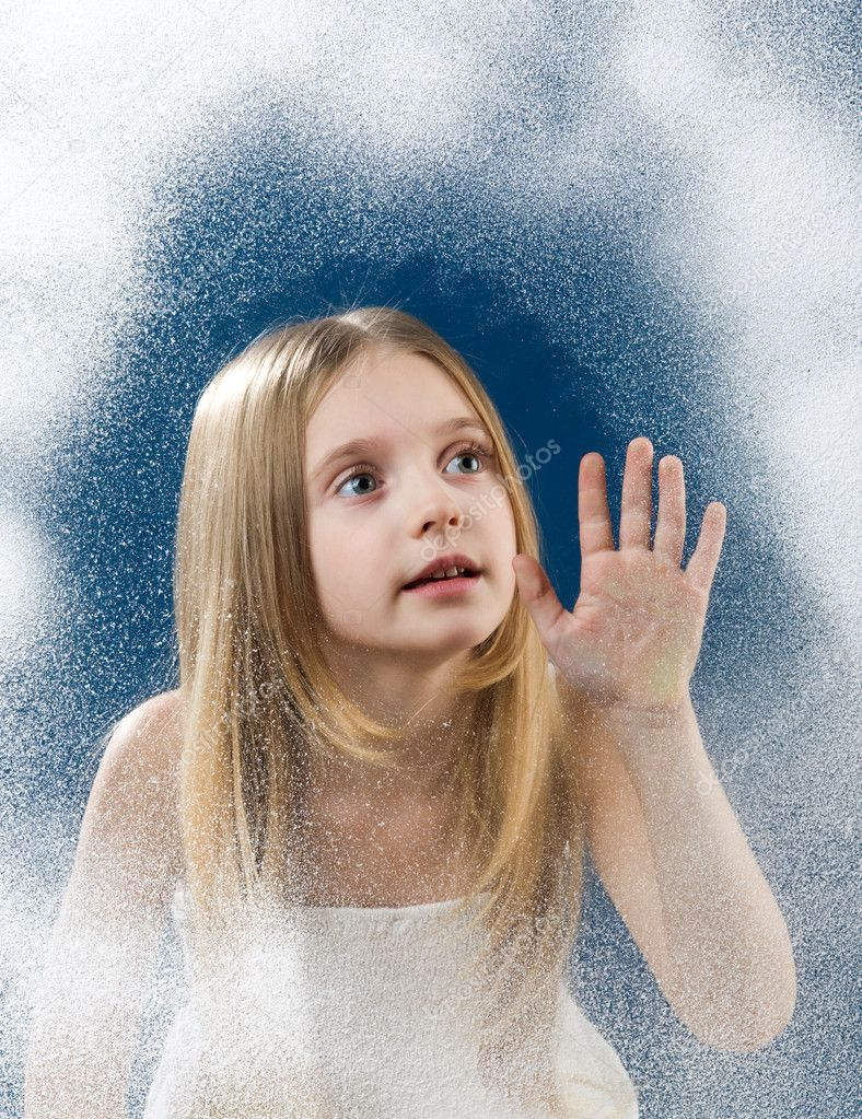Amazed little girl looking upwards through frosty window touching it by hand — Stock Photo #10713192