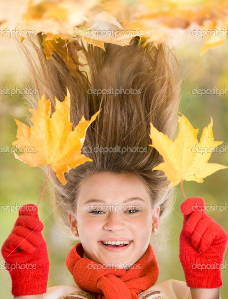 Portrait of laughing young girl holding two maple leaves — Stock Photo #10713291