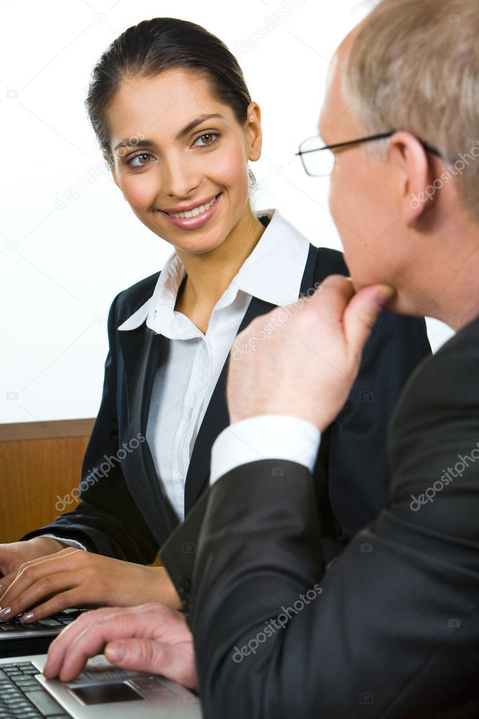 Portrait of beautiful smiling woman in suit looking at her elderly boss while typing on the laptop — Stock Photo #10714084