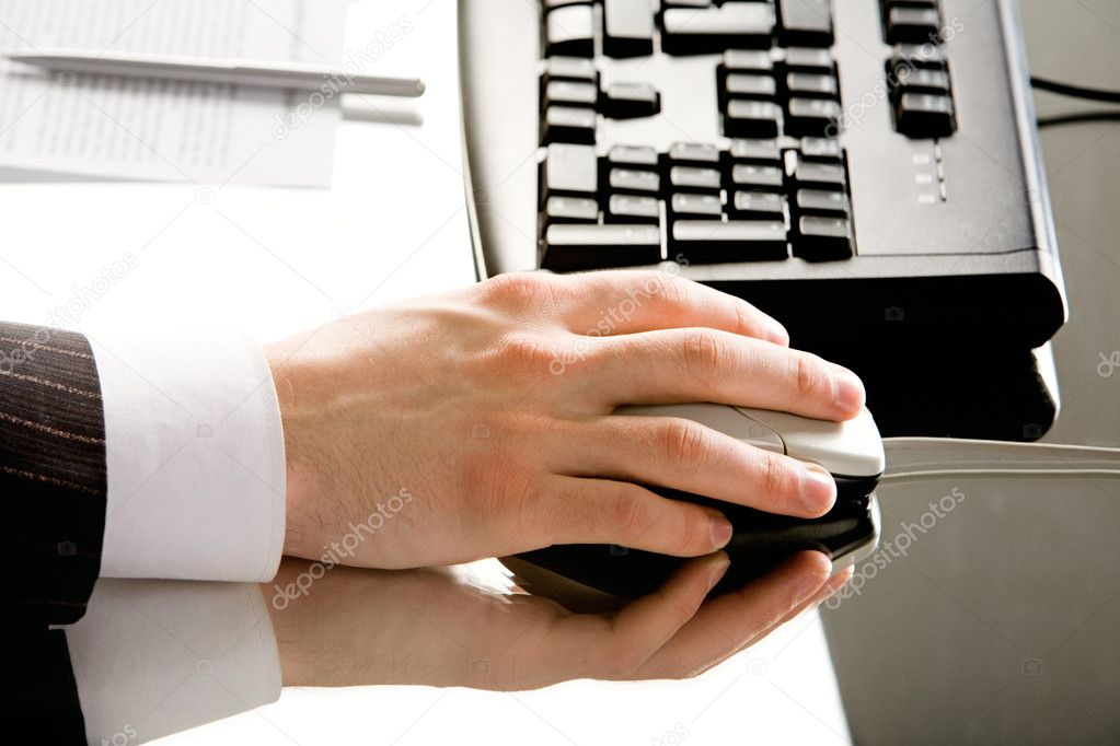 Image of hand with computer mouse placed on a working table — Stock Photo #10715904