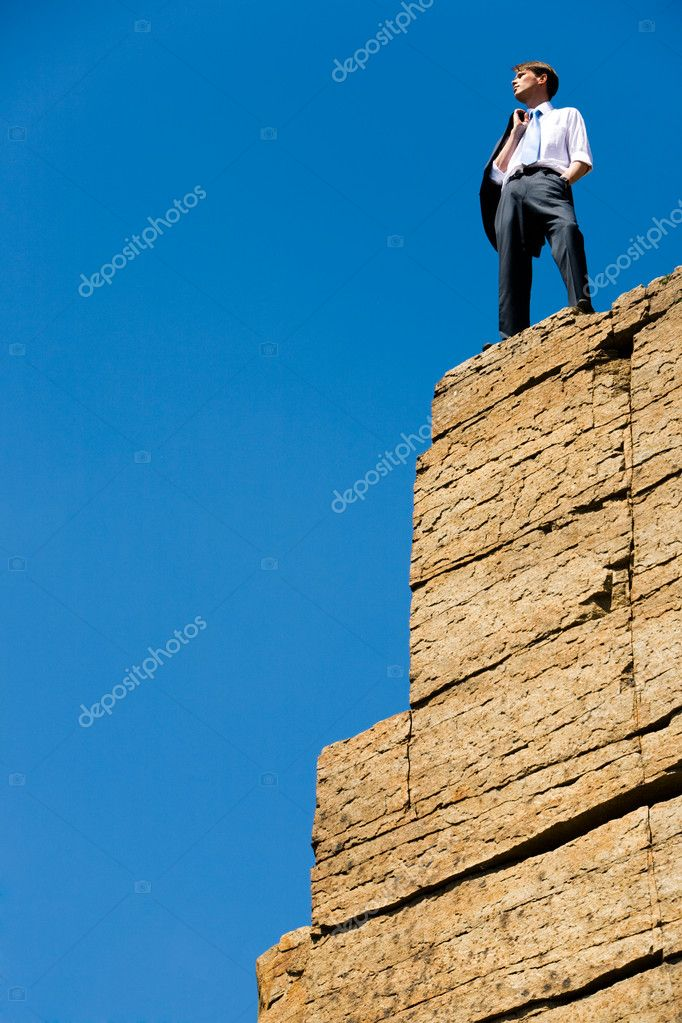 Image of confident businessman standing on the mountain top with navy blue sky over him — Stock Photo #10716646