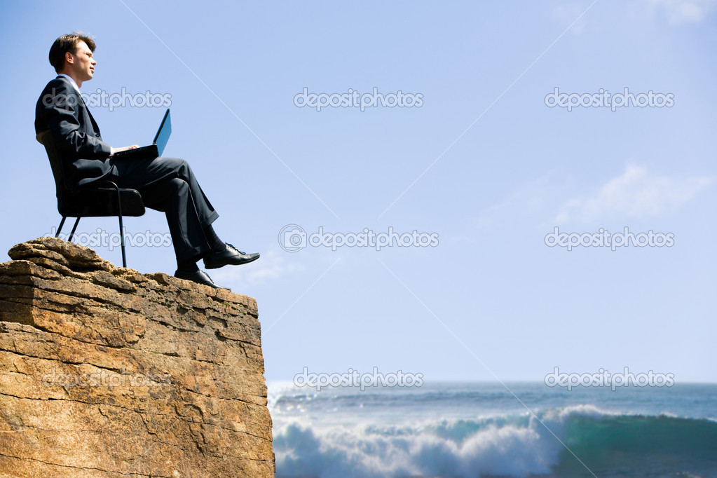 Image of confident business man sitting on the top of rock with laptop and looking at sea below — Stock Photo #10716654