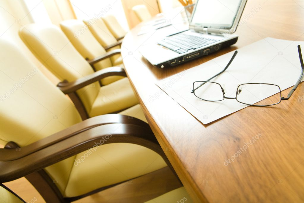 Image of table with laptop, papers, glasses on it with chairs near by in row — Stock Photo #10716721