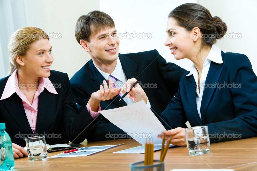 Portrait of three white-collar workers sitting at table and working with documents in the office — Stock Photo #10717796