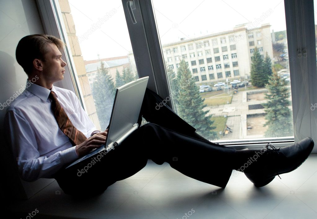 Photo of smart businessman sitting on window-sill with laptop and looking through window — Stock Photo #10718332