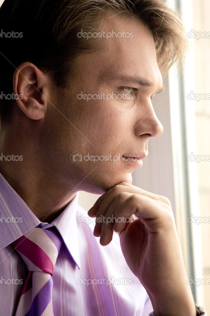 Profile of thoughtful male touching his chin and looking through window — Stock Photo #10718335