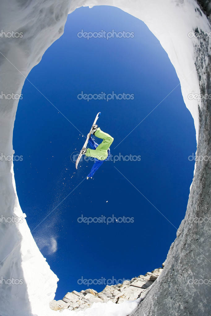 Below view of fearless sportsman jumping high over snow covered mountains on snowboard  Stock Photo #10719365