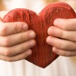 Red wooden heart in child's hands — Stock Photo #10730371