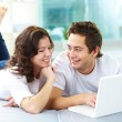 Couple using laptop - Stock Photo