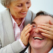 Pretty senior wife closes husband's eyes by hands — Stock Photo