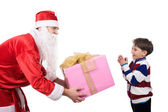 Happy lad looking at big giftbox in Santa's hands — Stock Photo