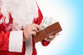 Santa's hands with wallet while counting money — Stock Photo