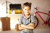 Portrait of cute boy looking at camera in garage — Stock Photo