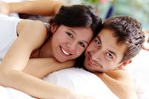 Happy couple lying in bed and looking at camera with smiles — Stock Photo