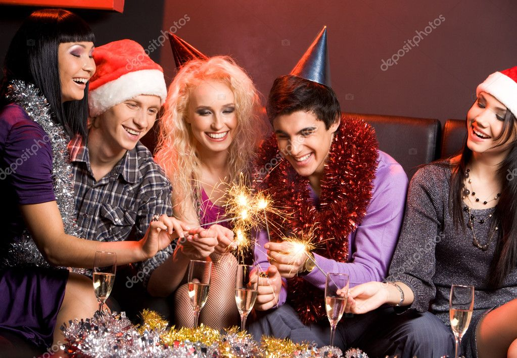 Group of friends looking at sparkling Bengal lights and laughing — Stock Photo #10730268