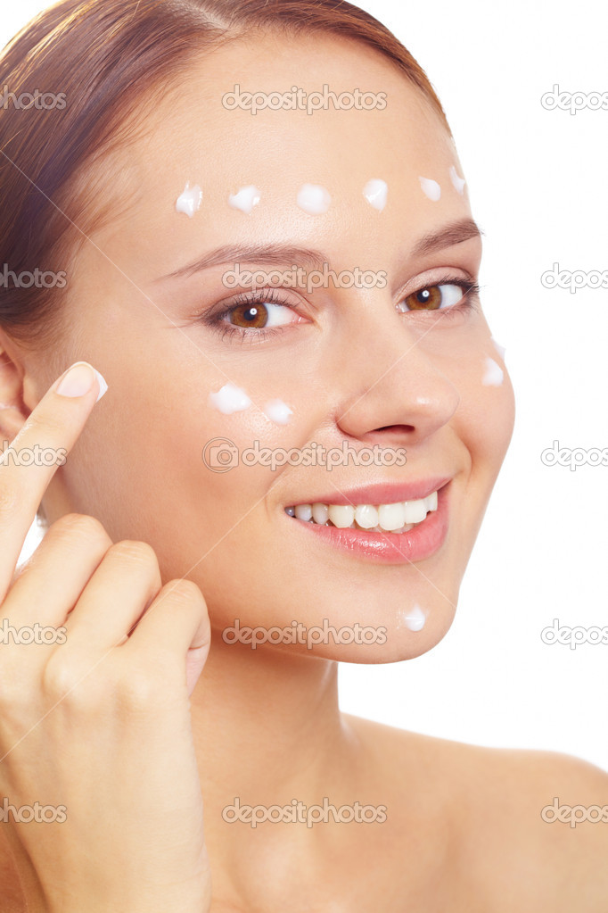 Fresh woman applying hydrating cream onto her face  Stock Photo #10730635