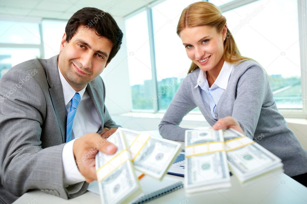 Two business partners at workplace giving money and looking at you — Stock Photo #10731526