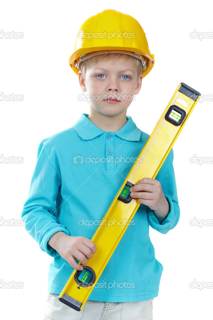 Cute boy in hardhat holding a level and looking at camera — Stock Photo #10732345