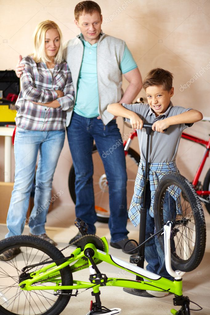 Portrait of cute boy pumping bicycle wheel with his parents on background  Stock Photo #10733144
