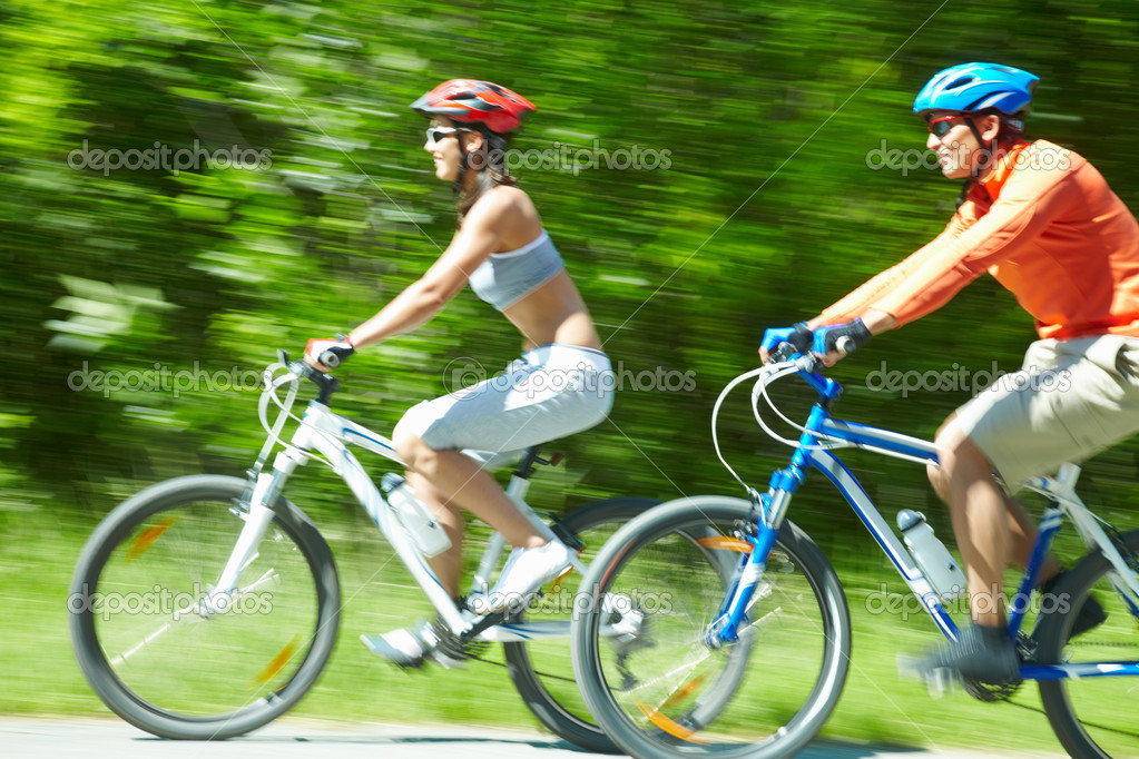 Image in motion of two bicyclists riding on country road — Stock Photo #10733156