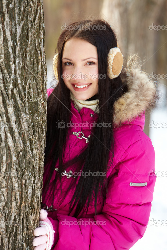 Portrait of pretty girl standing by tree trunk in winter park and looking at camera  Stock Photo #10733550