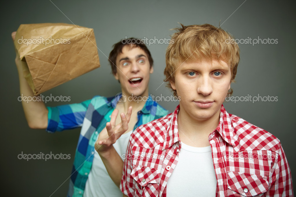 Crazy guy being ready to explode paper bag behind his friend back — Stock Photo #10733650