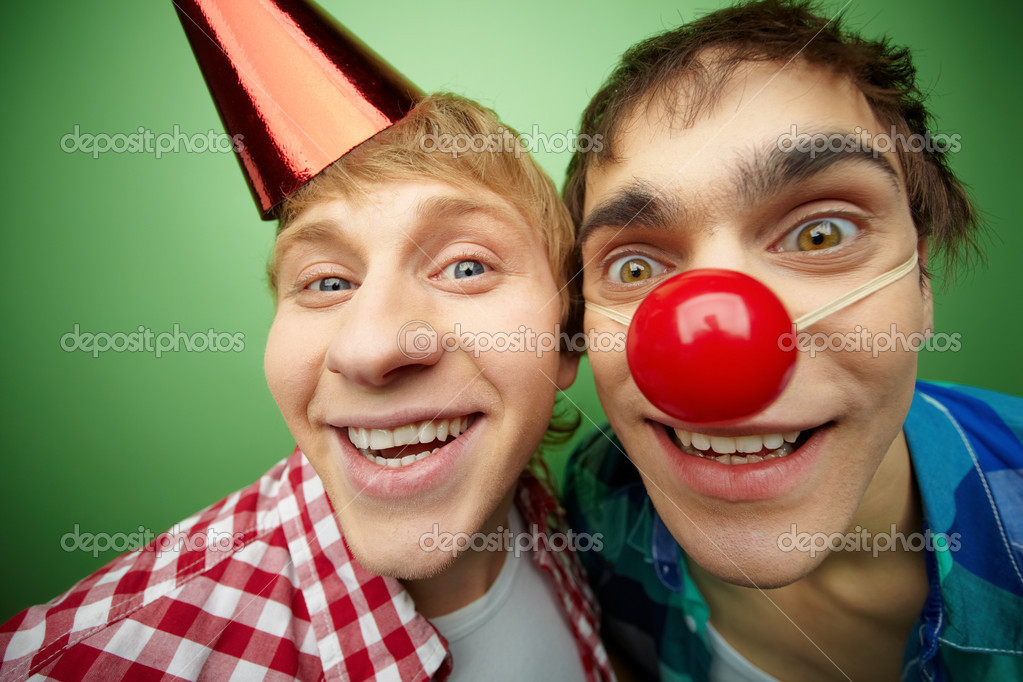 Two crazy guys making faces at camera on fool's day, isolated on green background — Zdjęcie stockowe #10733657