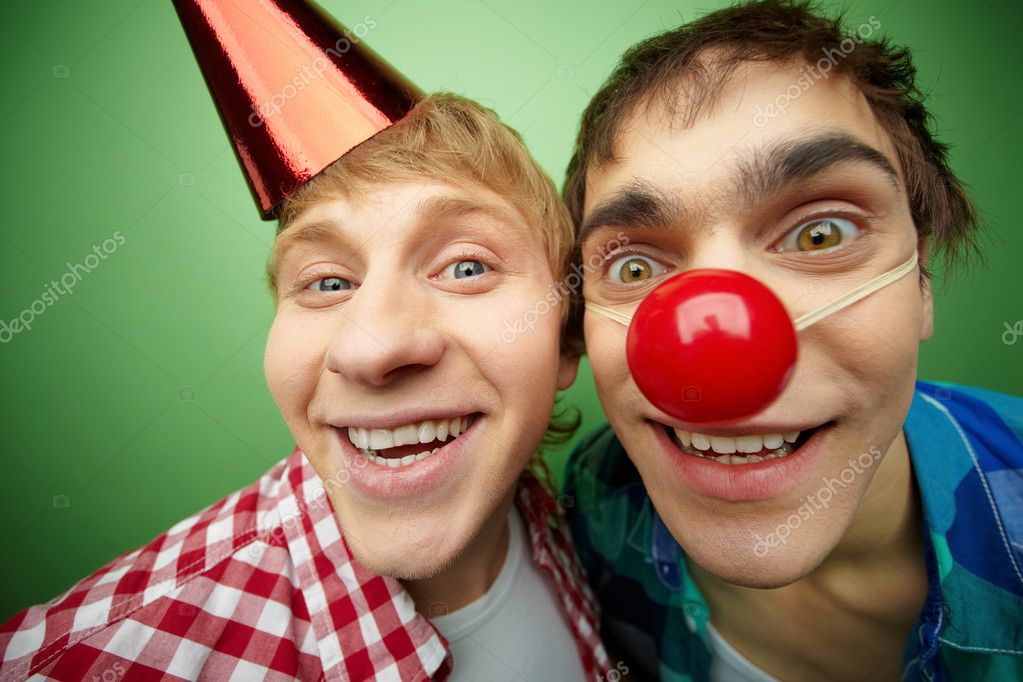 Two crazy guys making faces at camera on fool's day, isolated on green background — Stock Photo #10733657