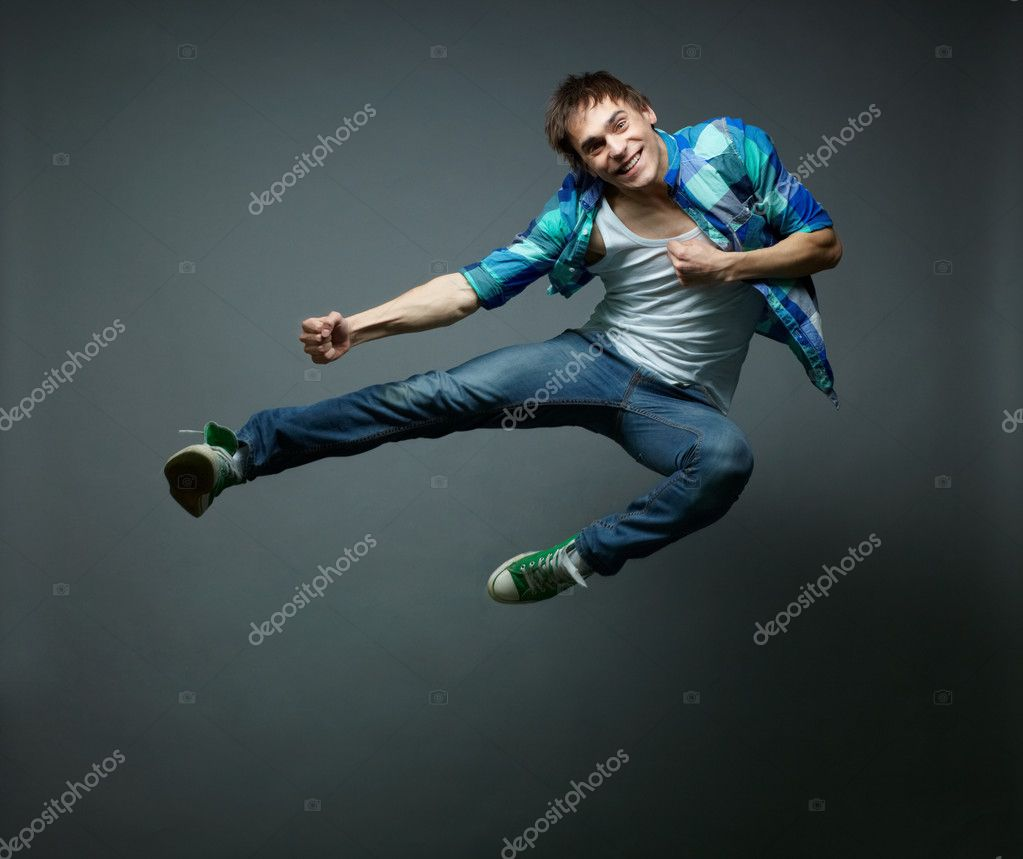 Guy with a wide smile jumping sideward and looking at camera — Stock Photo #10733690
